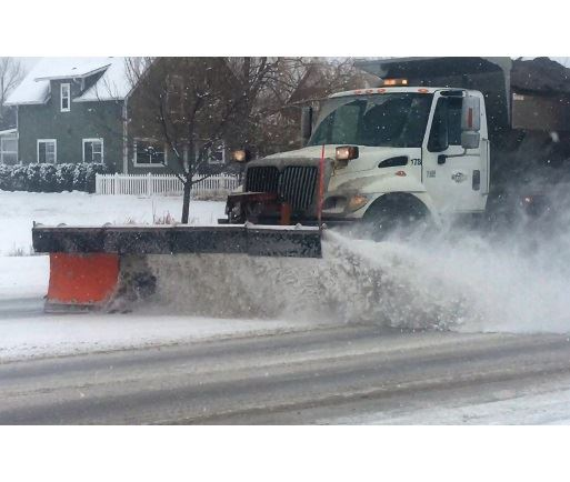 Snow plow clearing the street on an overcast day