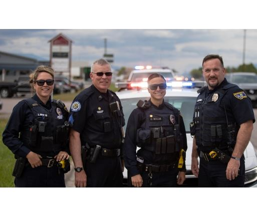 Four smiling police officers posing in front of patrol cars